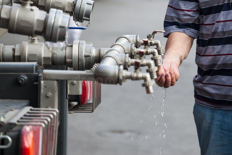 Golpecito de agua hecho de varios tubos, con las manos intentando sostener el agua para ahorrarla y para beberla Este grifo distr fotografía de archivo libre de regalías