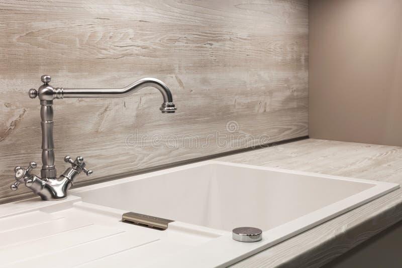 Golpecito de agua moderno del cromo del diseñador sobre el fregadero de cocina blanco fotos de archivo