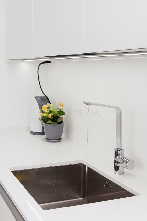 Golpecito de agua moderno del cromo del diseñador sobre fregadero de cocina del acero inoxidable Interior de la cocina blanca bri foto de archivo