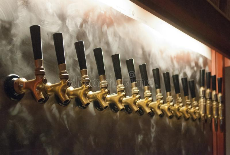 Golpecitos de cobre amarillo de la barra de la cerveza foto de archivo