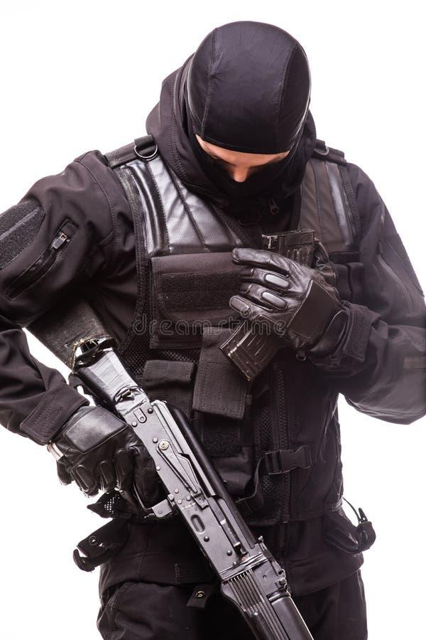 GOLPEE CON FUERZA al oficial con el rifle de asalto en el uniforme del negro aislado en blanco imágenes de archivo libres de regalías