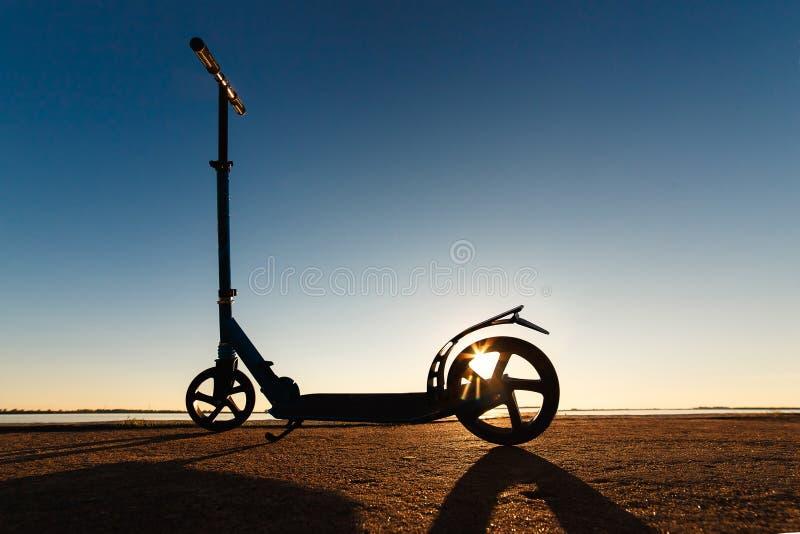 Golpee la vespa con el pie en pista corriente del asfalto, bajo luz del sol en el día de verano soleado foto de archivo libre de regalías