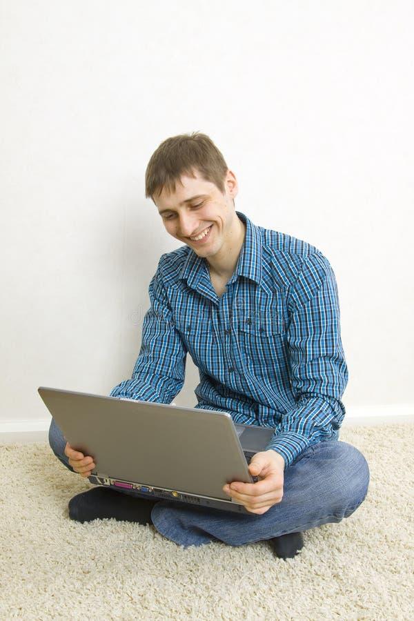 Golvbärbar datorman som sitter genom att använda