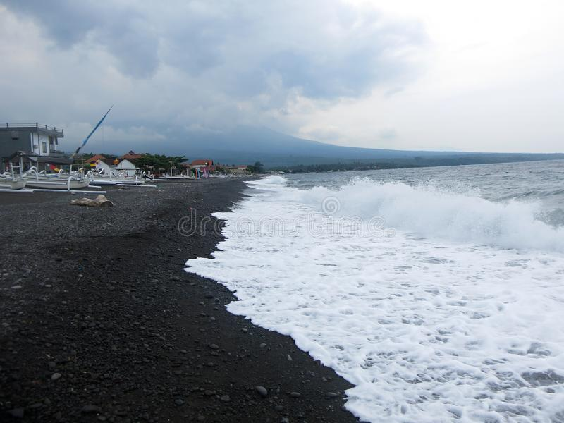 Golven, brandings en overzees schuim dat het zandige zwarte vulkanische zandstrand van Bali raakt In Amed, is het overzees stil,  royalty-vrije stock afbeelding