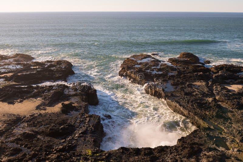 Golven in de onderbrekingen van een waterinham tegen de rotsen op het Toneelgebied van Kaapperpetua stock afbeeldingen