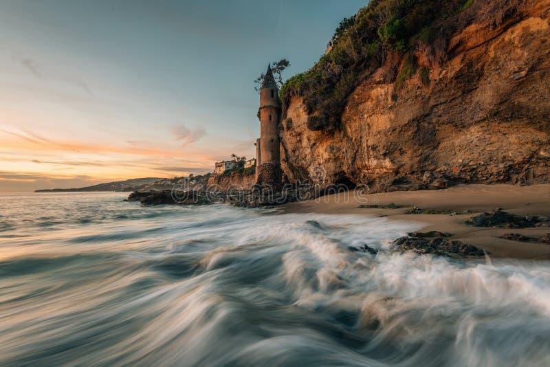 Golven in de Vreedzame Oceaan en de Piraattoren bij zonsondergang, in Victoria Beach, Laguna Beach, Californië stock afbeeldingen