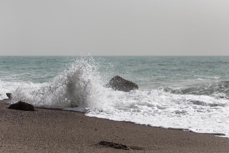 Golven die bij de kust bij zandig strand verpletteren royalty-vrije stock afbeeldingen