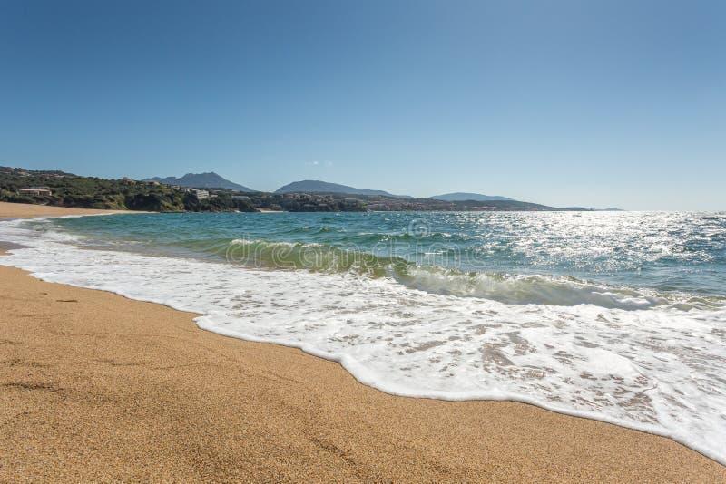 Golven die het strand omwikkelen in Propriano in Corsica stock foto's