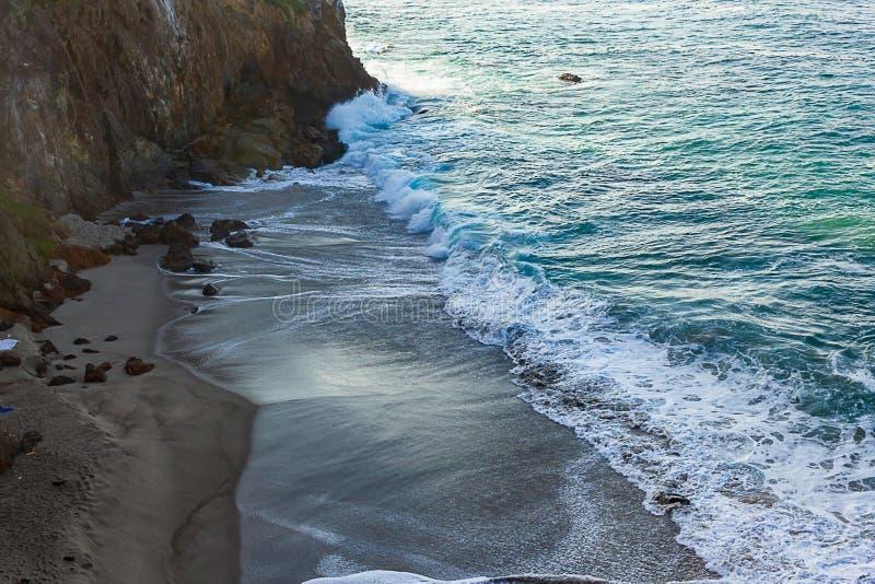 Golven die met schuim op zandig strand met terugslag tegen klippenmuur breakaing stock fotografie