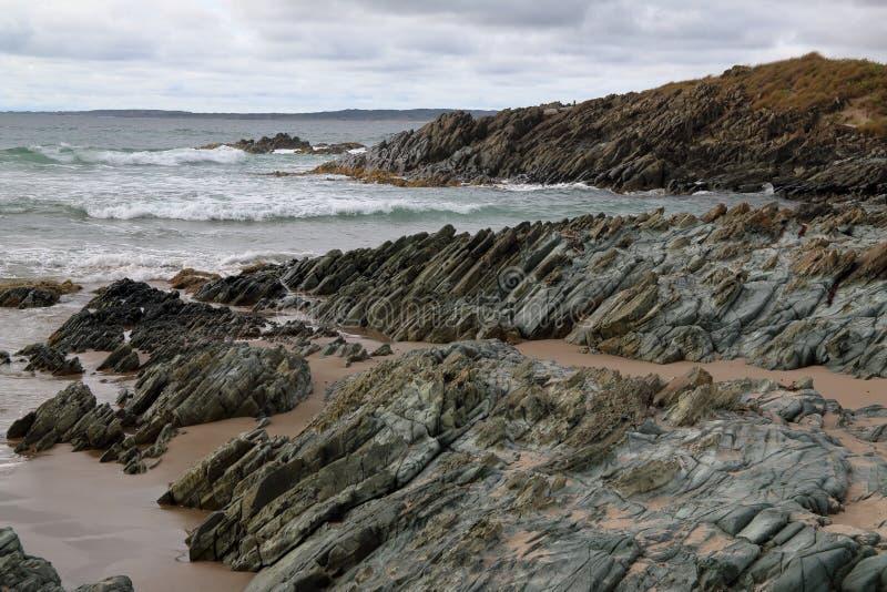 Golven die oceaanrotsen, op afgelegen Arthur Pieman Conservation-gebied, de Westkust van Tasmanige verpletteren stock foto's