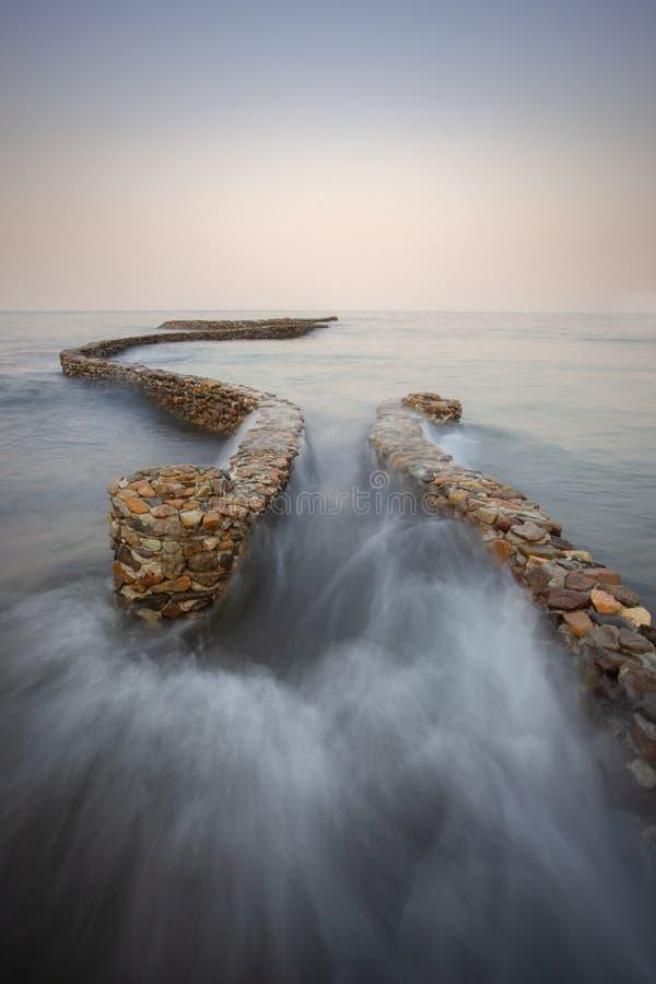 Golven die op de Golfbreker breken stock foto