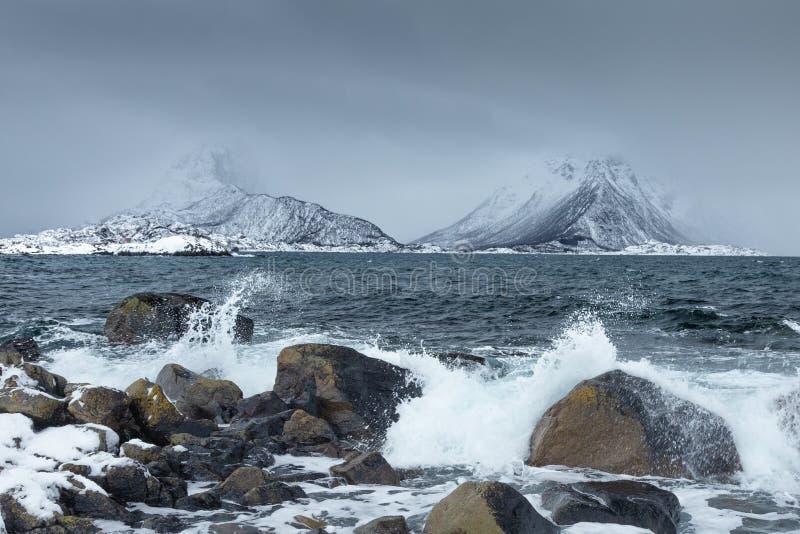 Golven die op de rotsen op een strand van Lofoten-Eilanden verpletteren, Noorwegen Spectaculaire sneeuwbergen op de achtergrond D stock foto's