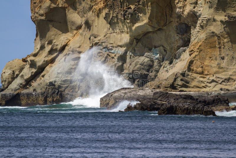 Golven die op de rotsen verpletteren stock afbeelding