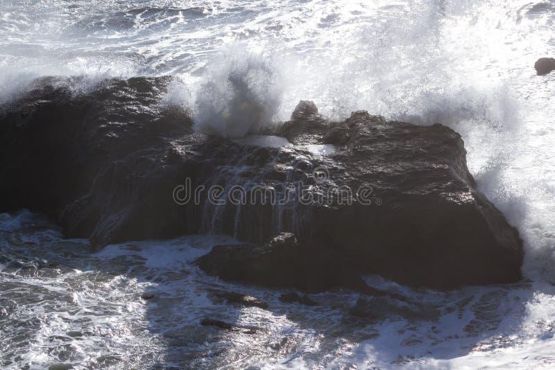 Golven die op de rotsen verpletteren royalty-vrije stock afbeelding