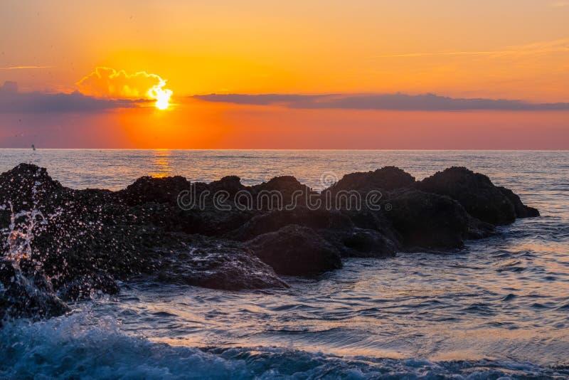 Golven die op een ertsader bij zonsopgang bespatten stock foto's