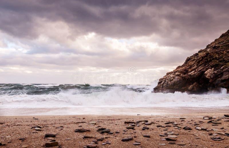 Golven die op een verlaten, dramatisch strand met donkere humeurige wolken in de hemel verpletteren stock foto's