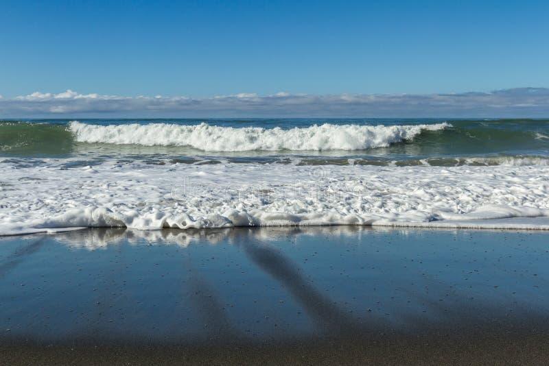 Golven die op het strand verpletteren stock fotografie