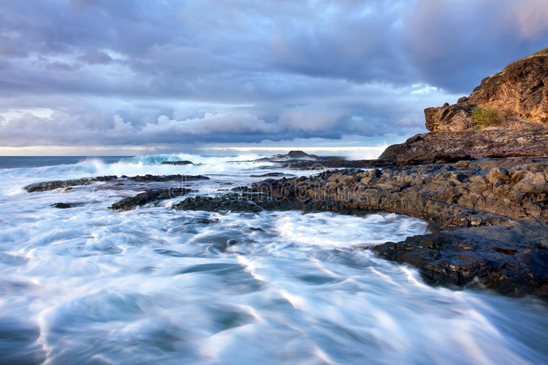 Golven die op rotsachtige kust breken stock foto's