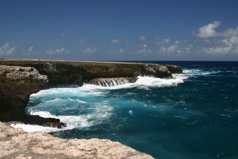 Golven die op rotsachtige kust verpletteren stock afbeelding