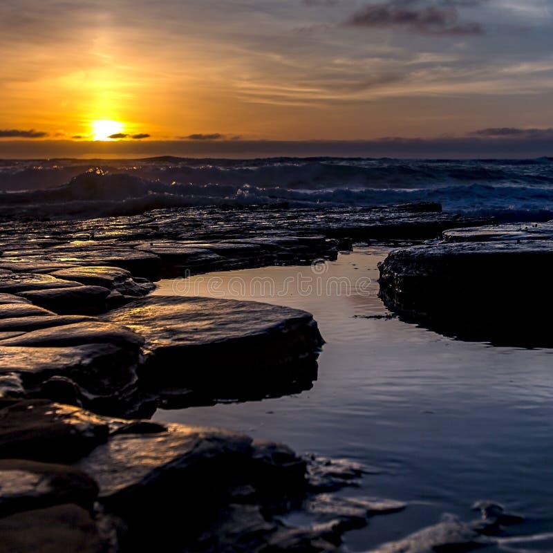 Golven die op rotsen met poolswater bij zonsondergang verpletteren royalty-vrije stock fotografie