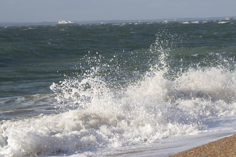 Golven die op strand verpletteren stock fotografie