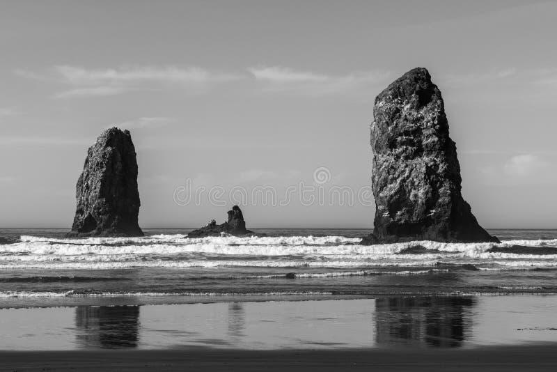 Golven die op verticale rotsen verpletteren die in Kanonstrand uitpuilen, Oregon, de V.S. stock fotografie