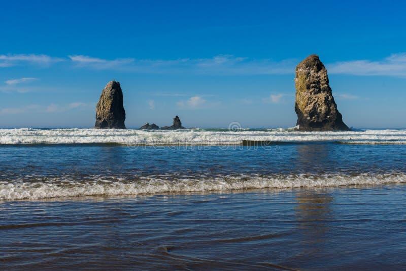 Golven die op verticale rotsen verpletteren die in Kanonstrand uitpuilen, Oregon, de V.S. royalty-vrije stock afbeelding