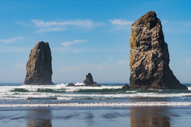 Golven die op verticale rotsen verpletteren die in Kanonstrand uitpuilen, Oregon, de V.S. royalty-vrije stock fotografie