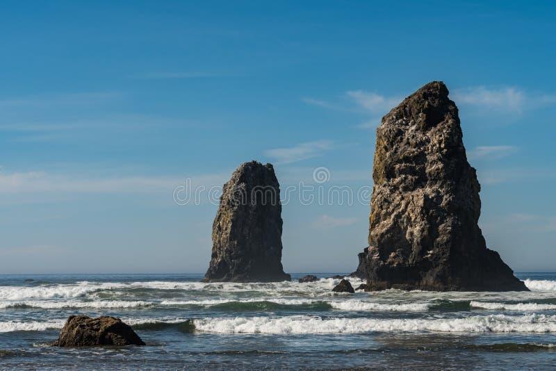 Golven die op verticale rotsen verpletteren die in Kanonstrand uitpuilen, Oregon, de V.S. stock foto's