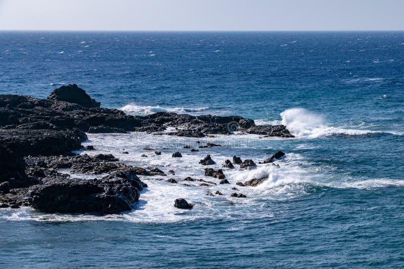 Golven die over de rand van de vulkanische rotsen van het lavagebied in Puerto DE Naos, La Palma breken, Canarische Eilanden stock foto