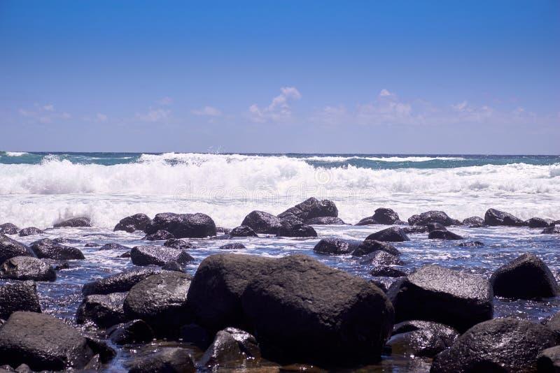 Golven die over rotsen op een zonnige dag breken royalty-vrije stock afbeelding