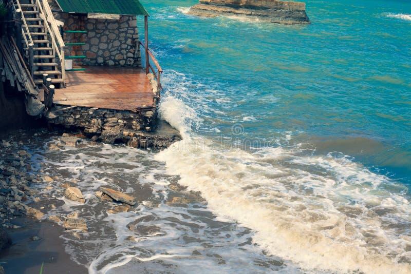 Golven die in Rotsen verpletteren Oceaanbeweging againts de stenen Blauwe Overzees die een Geruïneerd Huis vernietigen Mediterraa royalty-vrije stock fotografie