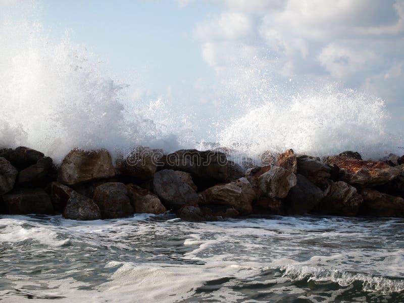 Golven die tegen rotsen en plonsenvlieg rond verpletteren Licht onweer op het overzees royalty-vrije stock afbeelding