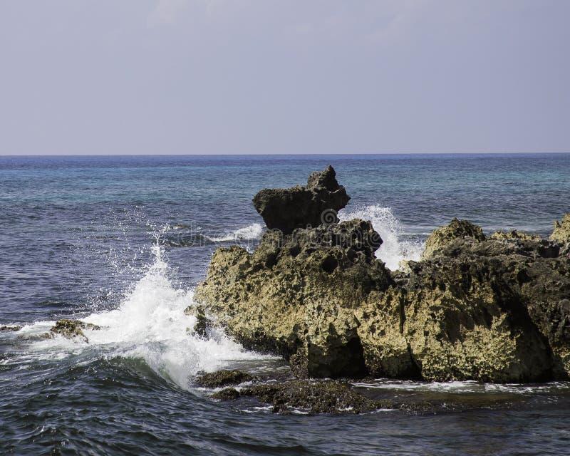 Golven die tegen rotsen verpletteren stock fotografie