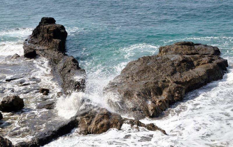 Golven die tussen rotsen bespatten royalty-vrije stock afbeelding