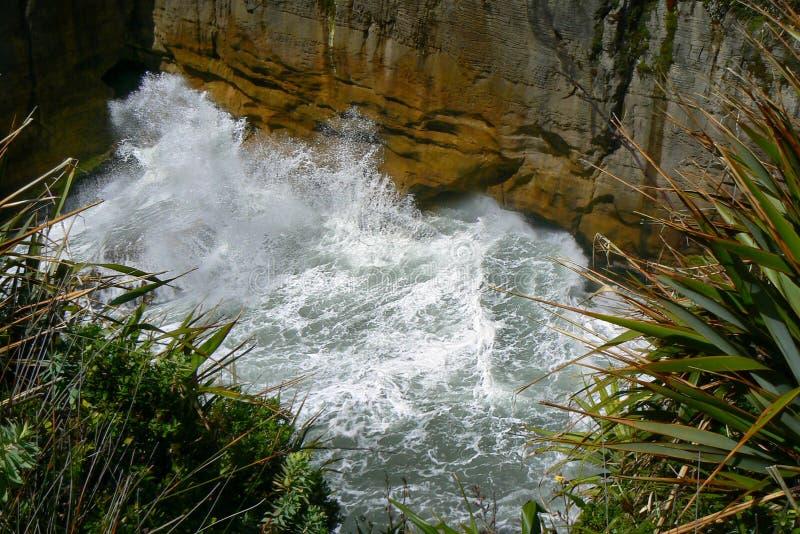 Golven die wild tegen rotsmuur, Punakaiki-Pannekoekrotsen en Gietgallen, het Nationale Park van Paparoa, Nieuw Zeeland verpletter stock foto's