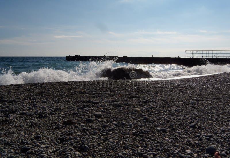 Golven en plonsen van overzeese branding en steen op de kust Stenen en shells op het strand royalty-vrije stock foto