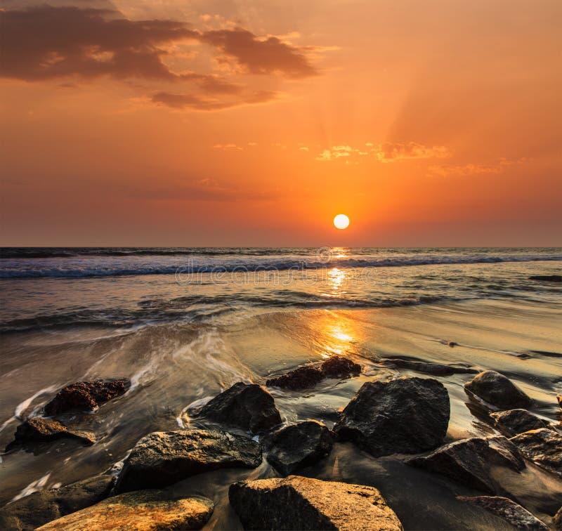 Golven en rotsen op strand van zonsondergang royalty-vrije stock afbeeldingen