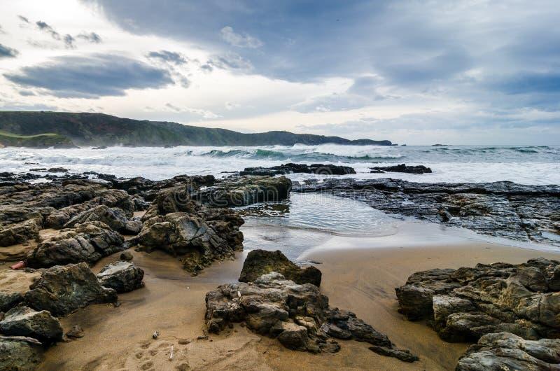 Golven op de kust in Verdicio-strand in Asturias Spanje Veranderlijke overzees in een maagdelijk strand met rotsen en schuim bij  stock afbeeldingen