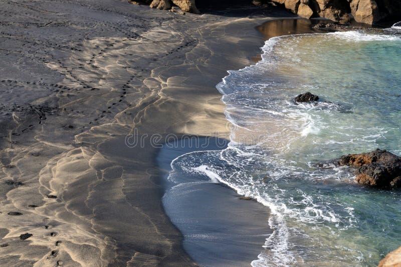 Golven op Multicolored strand royalty-vrije stock foto's