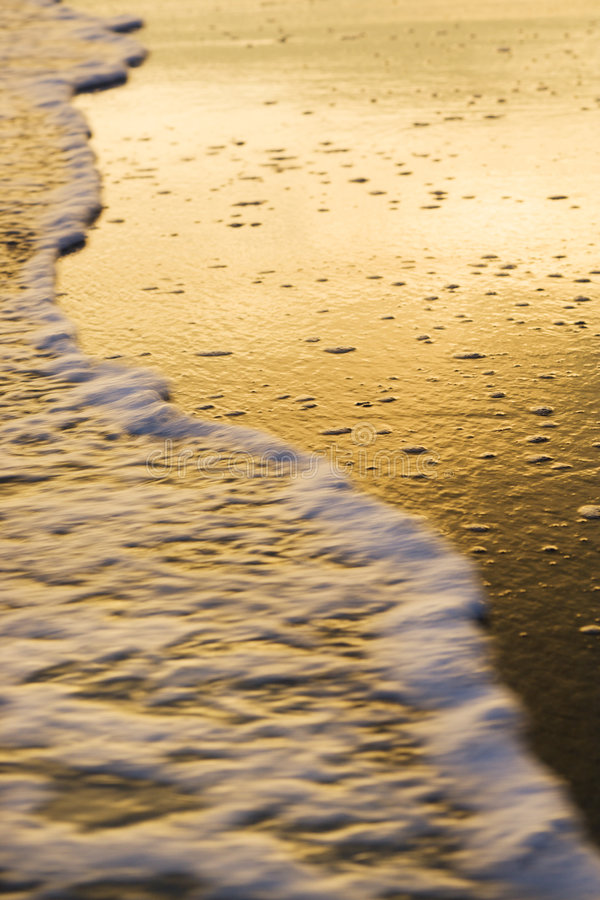 Golven op strand bij zonsondergang. stock foto's