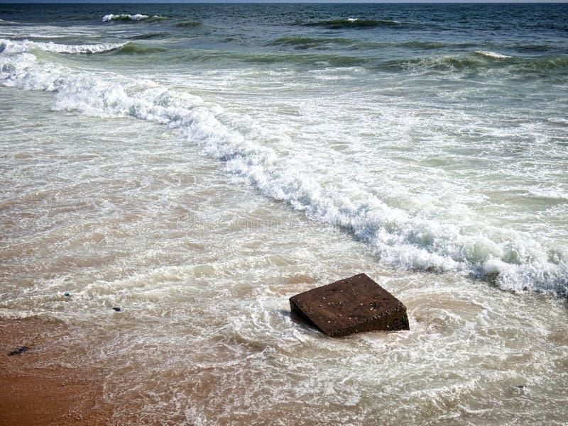 Golven op strand en kubus stock foto