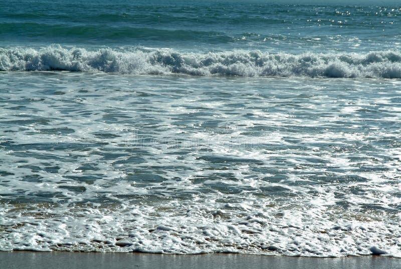Golven in strand stock foto's