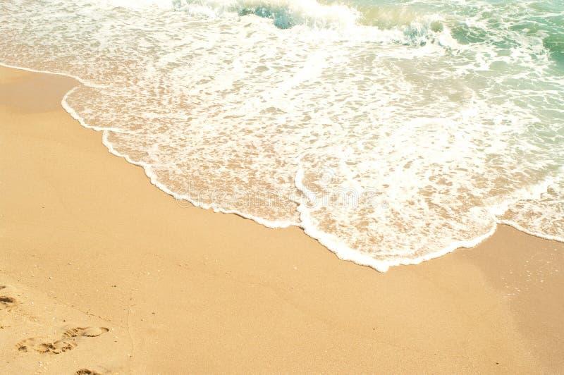 Golven van overzees en geel zand royalty-vrije stock afbeeldingen