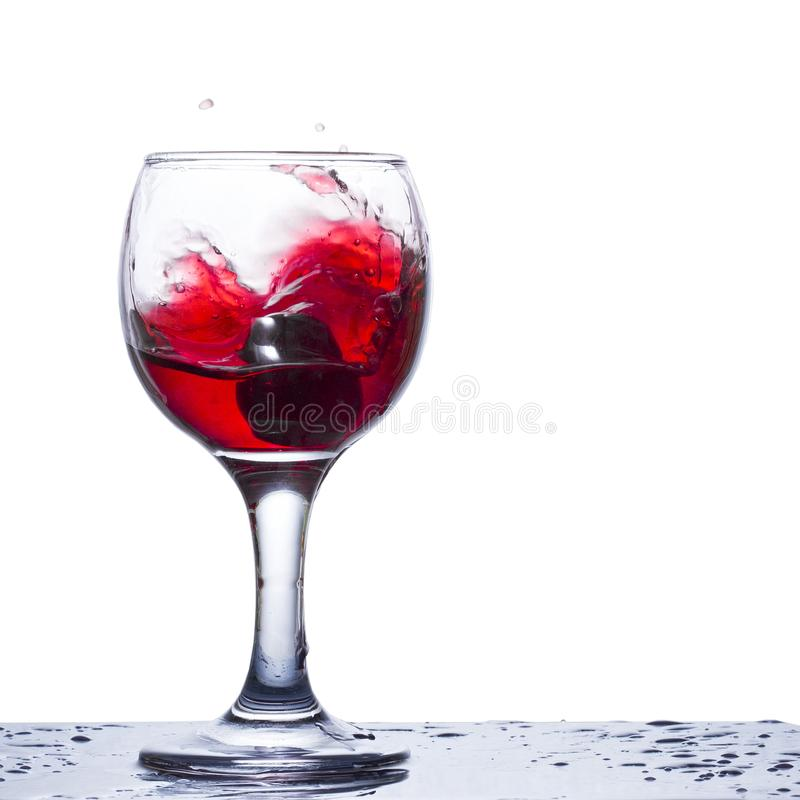 Golven van rode wijn in een glas op een witte achtergrond stock foto