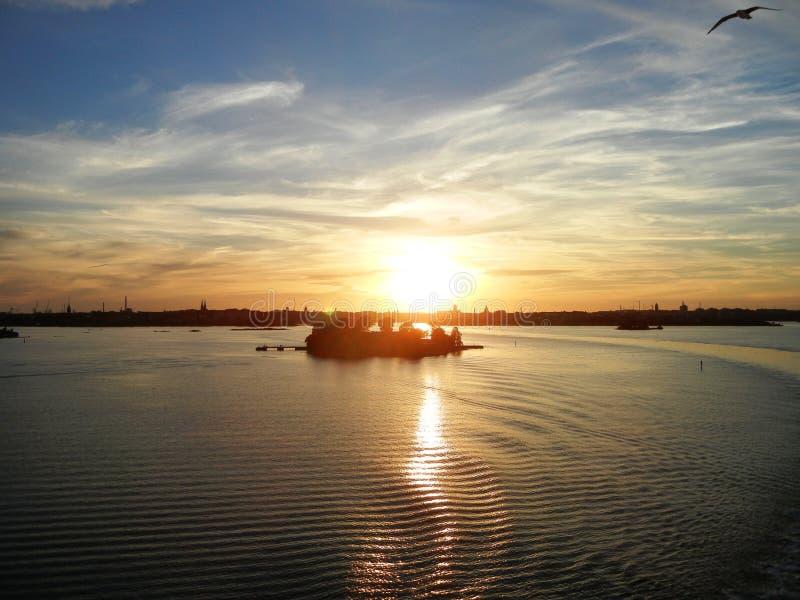 Golvend water, wolken in een een zonsondergang en panorama van Helsinki royalty-vrije stock afbeeldingen