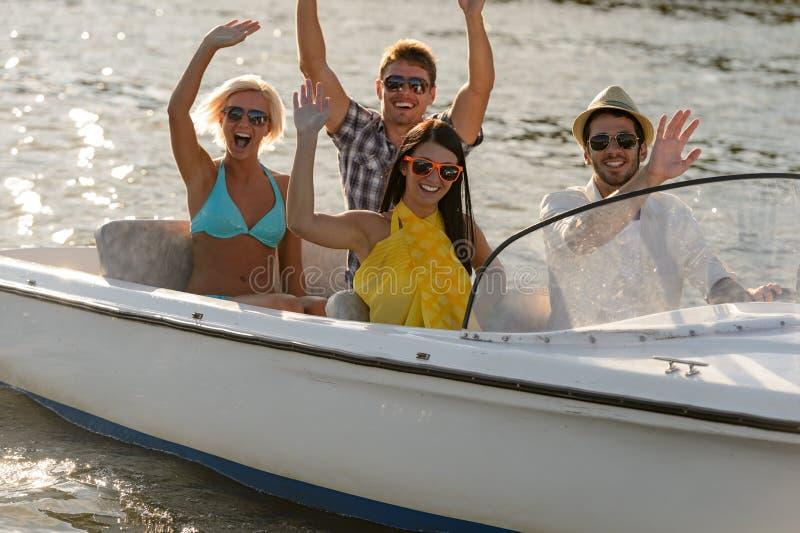 Golvende jonge mensen die in motorboot zitten royalty-vrije stock foto's