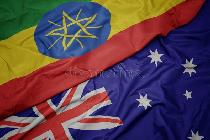 golvende kleurrijke vlag van Australië en nationale vlag van Ethiopië stock foto