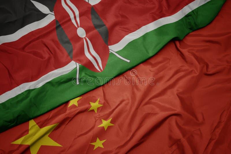 golvende kleurrijke vlag van China en nationale vlag van Kenia stock foto