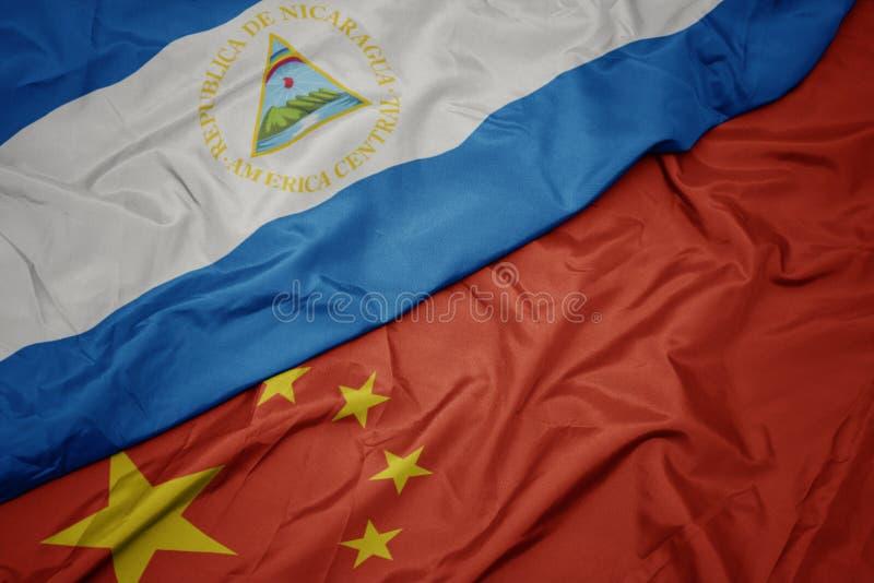 golvende kleurrijke vlag van China en nationale vlag van Nicaragua stock fotografie